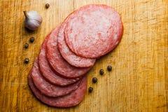 Dünn geschnittene Stücke Salami auf einem Schneidebrett Lizenzfreies Stockfoto