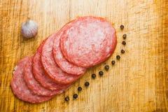 Dünn geschnittene Stücke Salami auf einem Schneidebrett Stockfoto