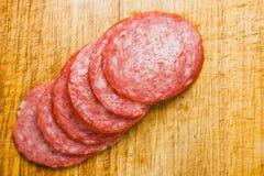 Dünn geschnittene Stücke Salami auf einem Schneidebrett Lizenzfreie Stockfotos