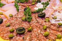 Dünn geschnittener Schinken und Salami mit Grüns Stockfotos