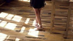 Dünne Ballerinabeine in den weißen Ballsaalschuhen bilden an der Ballettklasse aus Ballerinapraxis im modernen Ballett stock footage