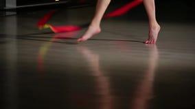 Dünne Beine der Nahaufnahme des Mädchenathleten, der Elemente der rhythmischen Gymnastik mit buntem Band durchführt