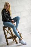 Dünne blonde Aufstellung auf Holzstuhl im Studio Lizenzfreie Stockfotografie