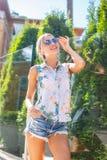 Dünne blonde Frau bei der Aufstellung der kurzen Jeanshose Lizenzfreie Stockfotos