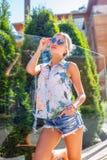 Dünne blonde Frau bei der Aufstellung der kurzen Jeanshose Stockfoto
