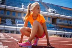 Dünne blonde Frau in der orange Sportkleidung Lizenzfreie Stockbilder