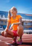 Dünne blonde Frau in der orange Sportkleidung Lizenzfreies Stockbild