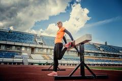 Dünne blonde Frau in der Sportkleidung, die Übungen tut Stockfotografie
