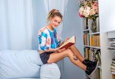 Dünne blonde Frau, die ein Buch liest Stockbilder