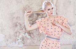Dünne blonde Frau im rosa Kleid Stockbild