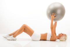 Dünne blonde Frauenübungen mit Eignungkugel lizenzfreies stockbild