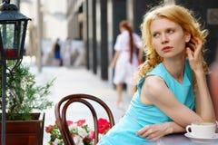 Dünne blonde junge Frau im blauen Kleid, das im Café sitzt Stockfotografie