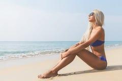 Dünne blonde langhaarige Frau im Bikini auf Strand Lizenzfreie Stockfotos