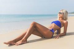 Dünne blonde langhaarige Frau im Bikini auf Strand Stockbilder