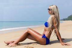 Dünne blonde langhaarige Frau im Bikini auf tropischem Strand Lizenzfreie Stockfotografie