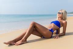 Dünne blonde langhaarige Frau im Bikini auf tropischem Strand stockbild
