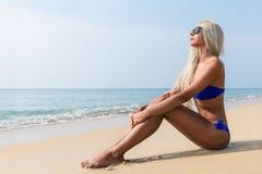 Dünne blonde langhaarige Frau im Bikini auf tropischem Strand Stockbilder