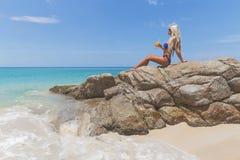 Dünne blonde langhaarige Frau im Bikini auf tropischem Strand Stockfotos
