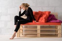 Dünne Blondine auf einem hölzernen Sofa in einer wehmütigen Haltung