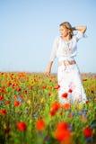 Dünne Frau auf dem Mohnblumegebiet Stockfotografie