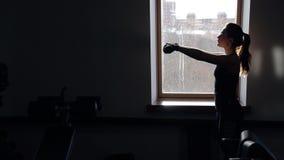 Dünne Frau der Junge recht tun Übungen mit Dummköpfen im Eignungsstudio stock footage