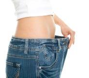 Dünne Frau, die übergroße Jeans zieht Stockfotos