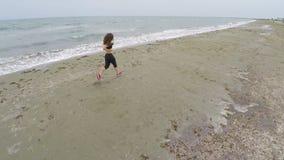 Dünne Frau, die entlang leeren Strand, Training läuft und Ansicht, Luftschuß genießt stock footage