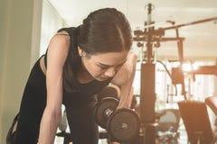 Dünne Frau hebt Gewichtsdummkopf in der Eignungsturnhalle an stockfotografie