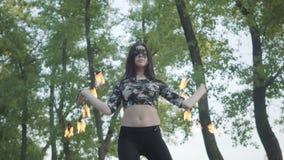 Dünne Frau im Maskentanzen, eine Show mit der Feuerkugel durchführend, die auf dem Riverbank steht Talentierte fireshow Künstlerv stock video