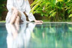 Frau, die am Pool mit Füßen im Wasser stillsteht. Lizenzfreies Stockbild