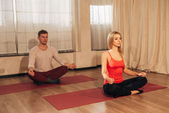 Dünne Frau und Mann auf Hintergrund meditierend in der Haltung von Lotos in der Turnhalle Stockfotos