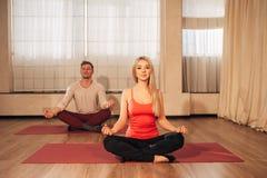 Dünne Frau und Mann auf Hintergrund meditierend in der Haltung von Lotos in der Turnhalle Lizenzfreies Stockbild