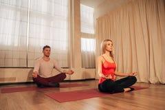Dünne Frau und Mann auf Hintergrund meditierend in der Haltung von Lotos in der Turnhalle Lizenzfreies Stockfoto