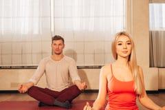 Dünne Frau und Mann auf Hintergrund meditierend in der Haltung von Lotos in der Turnhalle Stockfoto