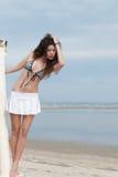 Dünne Frauenhaltung durch das Meer, das Minirock und BH trägt Stockfotografie
