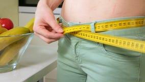 Dünne Frauenmaßtaille auf dem Hintergrund einer Platte mit Obst und Gemüse, ein gesunder Lebensstil stock video