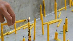 Dünne gelbe Wachskerze beleuchtet eine andere Kerze mit seiner Flamme Viele dünnen gelben Wachskerzen stock footage