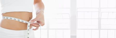 Dünne gesunde Frau mit messendem Band mit Fenstern Stockfoto