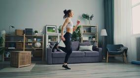 Dünne junge Dame konzentrierte sich auf Betrieb sofort trainierend in der hellen Wohnung stock video