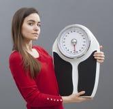 Dünne junge Frau, die ihre Skala mit Stolz für Gewichtskontrolle hält Stockfotografie