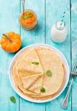 Dünne Krepps oder Pfannkuchen mit frischem Kürbisconfiture, -stau und -flasche Milch auf einer Draufsicht des rustikalen hölzerne Lizenzfreies Stockbild