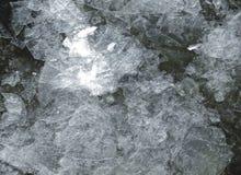Dünne lichtdurchlässige Eiszapfen auf der Wasseroberfläche im Vorfrühling lizenzfreies stockbild