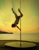 Dünne Mädchenübungsstangentanz auf einer Sonnenuntergangseelandschaft. Lizenzfreie Stockfotografie