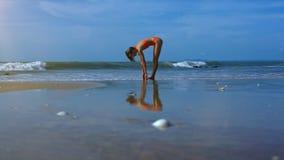 Dünne Mädchen-Zahl in der Yoga-Haltung zeigt im Wasser auf Strand-Sand stock video footage