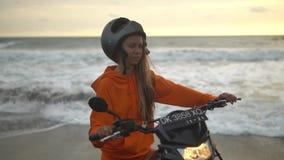 Dünne Mädchenstellung unter dem rasenden Meer, gekleidet in einem orange Hoodie, schwarzer Sturzhelm auf ihrem Kopf, Hände, die a stock video footage