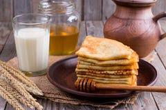 Dünne Pfannkuchen auf einer Platte mit Honig und einem Glas Milch auf einem hölzernen Hintergrund Geschmackvolles Frühstück Lizenzfreies Stockbild