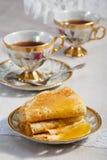 Dünne Pfannkuchen auf einer Platte und einer Tasse Tee Lizenzfreie Stockfotografie