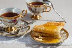 Dünne Pfannkuchen auf einer Platte und einer Tasse Tee Stockfotos