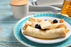 Dünne Pfannkuchen mit Beeren und Butter auf Platte Stockfotos