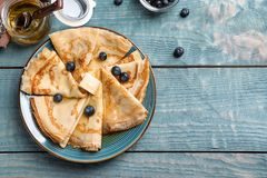 Dünne Pfannkuchen mit Beeren und Butter auf Platte Stockbild
